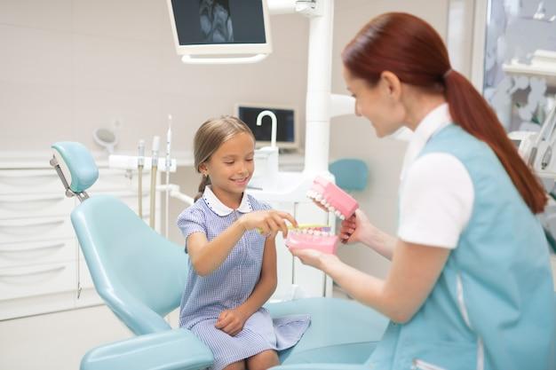 Dentista dando aula. dentista infantil profissional ruivo dando aula de escovação de dentes para menina
