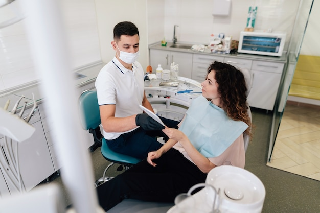 Dentista dando espelho para paciente no consultório