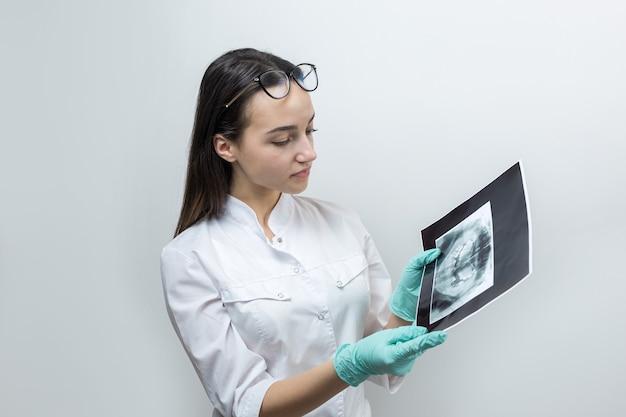 Dentista de garota com um jaleco branco segura uma foto dos dentes do paciente.
