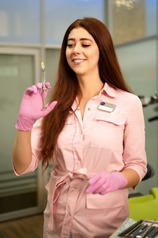 Dentista de menina bonita tem uma seringa na mão. sorrindo e olhando para a câmera. anestesia e injeções em odontologia.