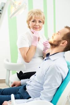 Dentista de mulher olhando para a câmera enquanto dava tratamento odontológico ao cliente masculino de uma odontologia moderna.