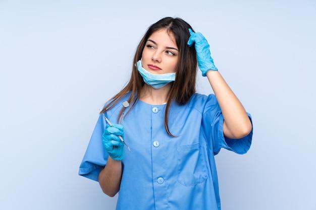 Dentista de mulher segurando ferramentas com dúvidas e com a expressão do rosto confuso