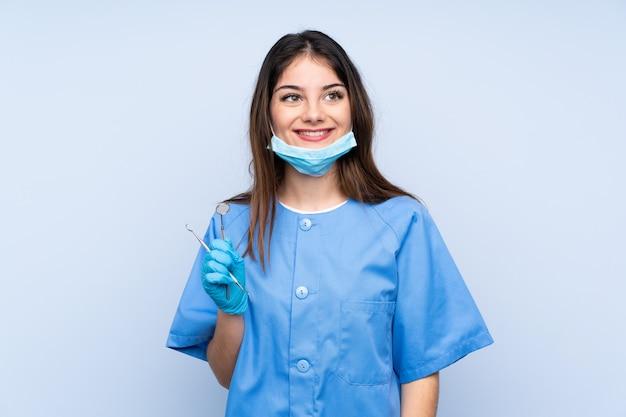 Dentista de mulher segurando ferramentas rindo e olhando para cima