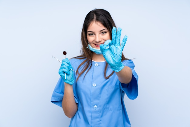 Dentista de mulher segurando ferramentas sobre parede azul, mostrando um sinal de ok com os dedos