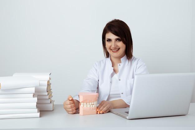 Dentista de mulher sentada à mesa no escritório com equipe odontológica isolada.