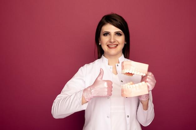 Dentista de uma linda mulher com material odontológico no estúdio rosa escuro.