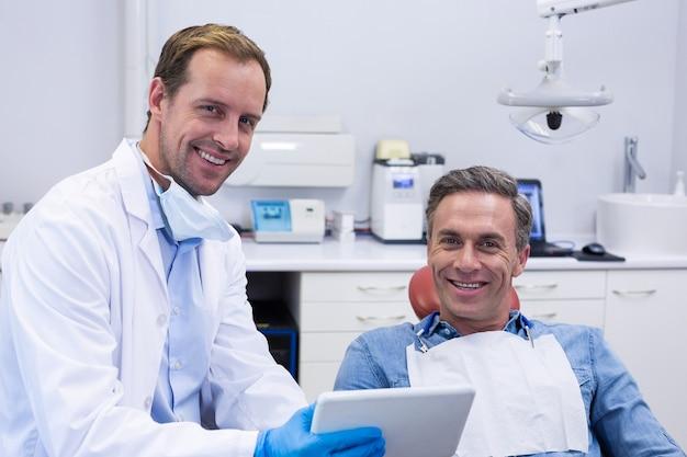 Dentista discutindo sobre tablet digital com paciente do sexo masculino
