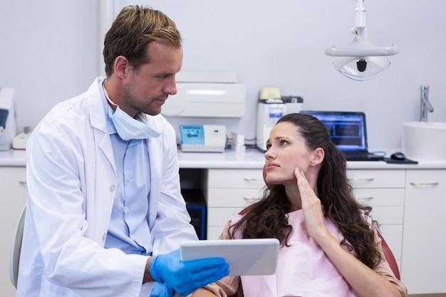 Dentista discutindo sobre tablet digital com paciente