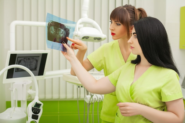 Dentista dois feminino no consultório odontológico, examinando os dentes do paciente