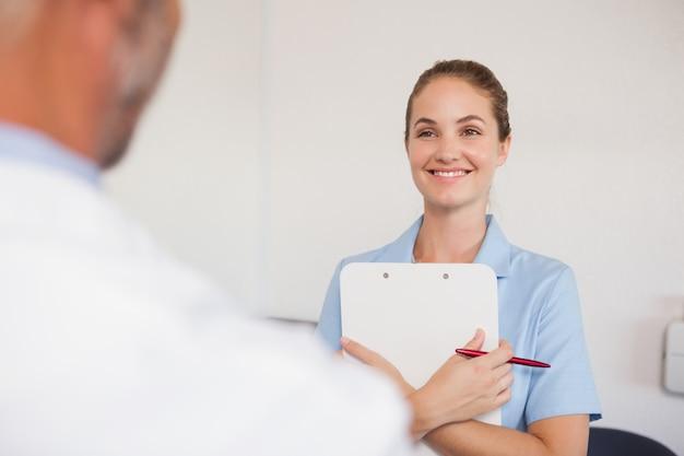 Dentista e assistente de frente para o outro