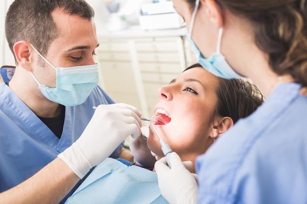 Dentista e assistente dental que examinam os dentes pacientes.