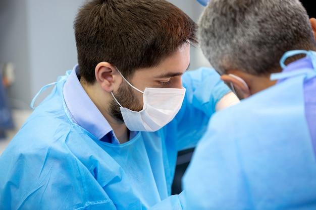 Dentista e assistente durante a cirurgia na clínica odontológica