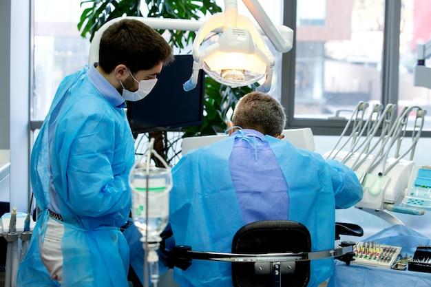 Dentista e assistente enquanto trabalha com um paciente