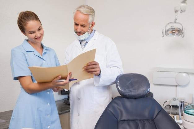 Dentista e assistente olhando o arquivo juntos