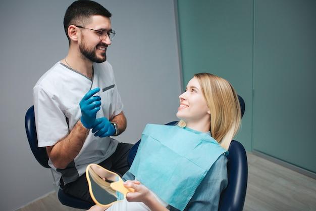 Dentista e cliente positivos alegres na odontologia. eles se entreolham e sorriem. cliente do sexo feminino sentar cadeira sin e detém um espelho. ela parece satisfeita.