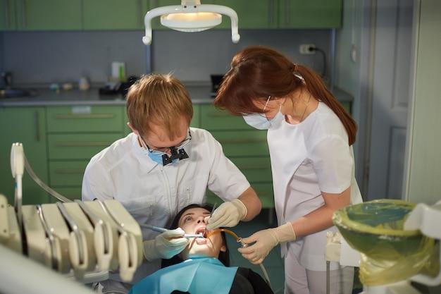 Dentista e enfermeira começam o tratamento no consultório odontológico