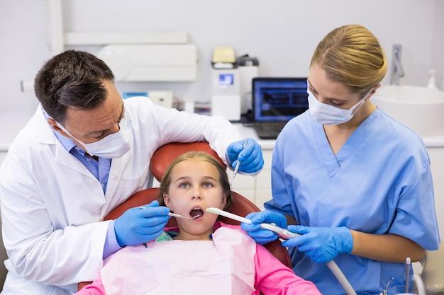 Dentista e enfermeira examinando um jovem paciente com ferramentas