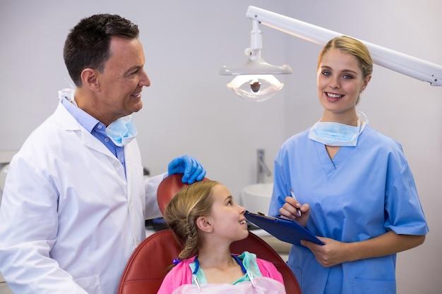 Dentista e jovem paciente olhando para a enfermeira