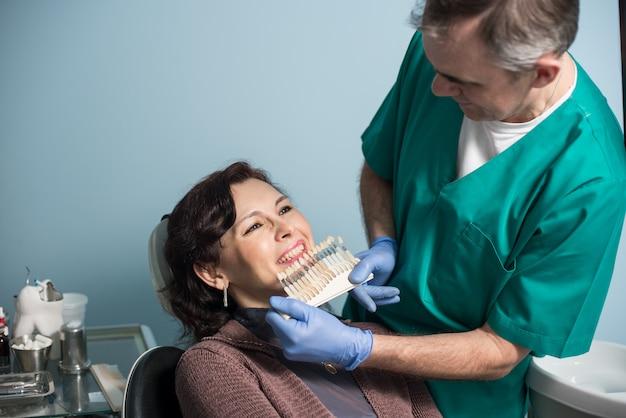 Dentista e paciente do sexo feminino, verificando e selecionando a cor dos dentes no consultório odontológico