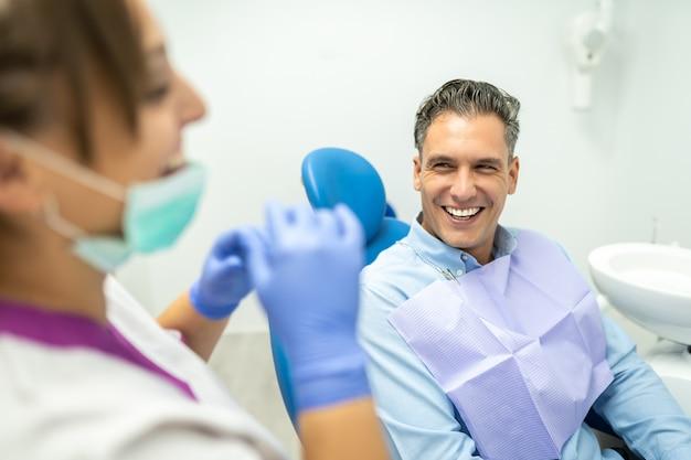 Dentista e paciente interagindo e sorrindo.