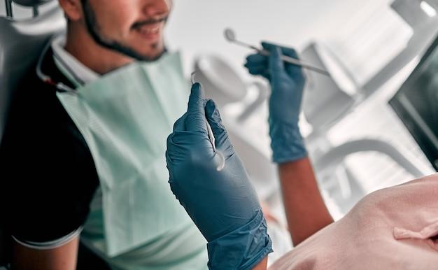 Dentista e paciente no consultório dentista. conceito de dentes saudáveis. foco seletivo do dentista em luvas de látex segurando um espelho dental perto do homem.