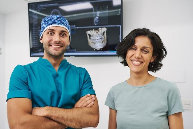 Dentista e paciente olhando para a câmera