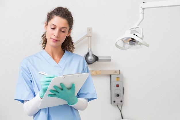 Dentista em azul esfrega a escrita na área de transferência