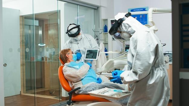 Dentista em equipamento de proteção aparecendo no raio-x dental de tablet, revendo-o com paciente sênior. equipe médica usando macacão de proteção facial, máscara, luvas, explicando a radiografia usando a tela do notebook