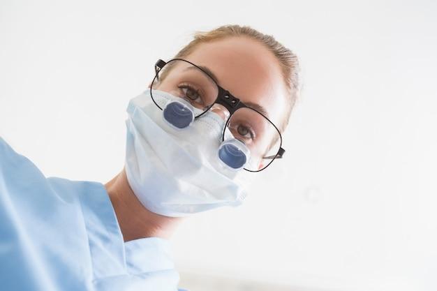 Dentista, em, máscara cirúrgica, e, lupas dentais, olhando baixo, sobre, paciente
