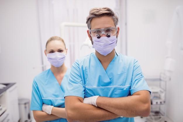 Dentista em pé com os braços cruzados na clínica odontológica
