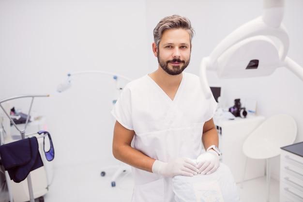 Dentista em pé na clínica