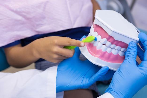 Dentista ensinando menino escovando dentes na clínica