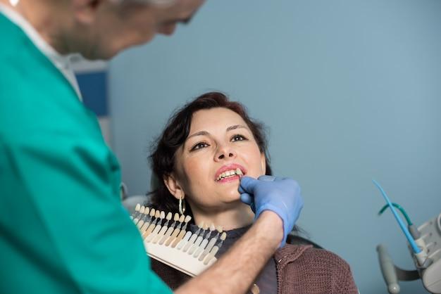 Dentista escolhendo a cor dos dentes de um paciente