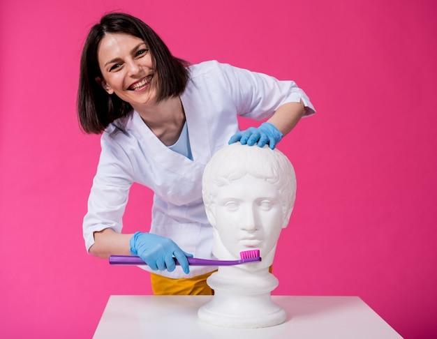 Dentista escovando os dentes de uma estátua antiga com uma escova de dentes grande