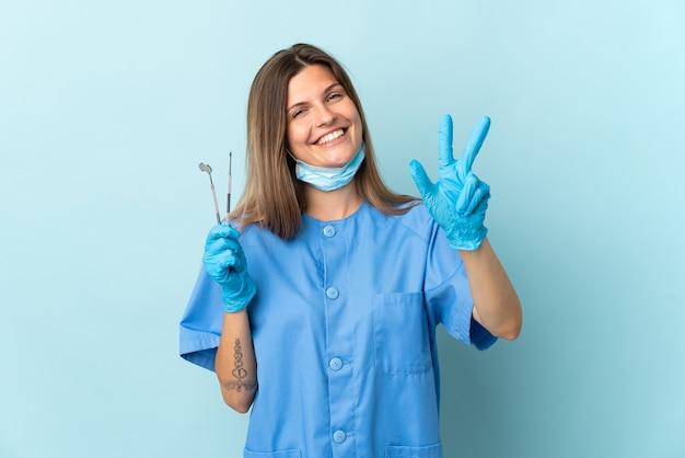 Dentista eslovaco segurando ferramentas isoladas em um fundo azul feliz e contando três com os dedos