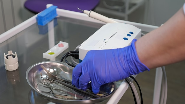 Dentista está pegando ferramentas da bandeja de metal na mesa de vidro, mão em closeup de luva de borracha azul. conceito de cuidados com os dentes.