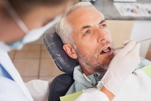 Dentista examinando dentes de pacientes na cadeira de dentistas