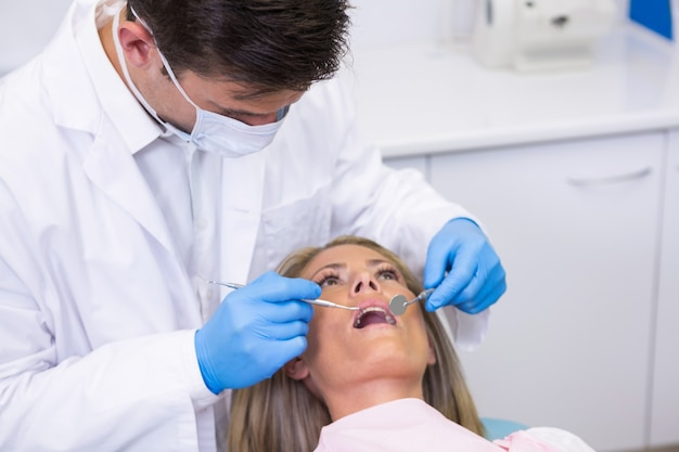 Dentista examinando mulher na clínica odontológica