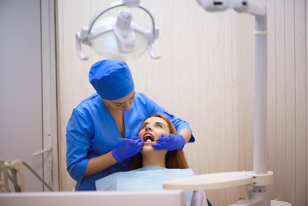 Dentista examinando os dentes de um paciente no dentista.
