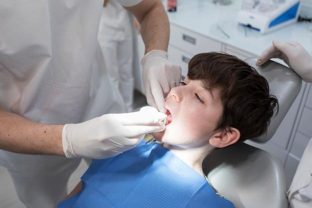 Dentista examinando os dentes do menino na clínica