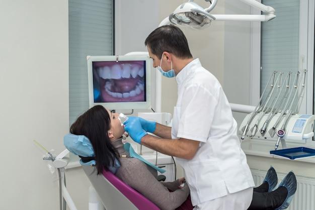 Dentista examinando os dentes do paciente com câmera intraoral