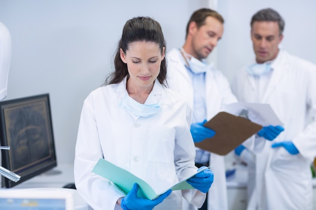 Dentista examinando relatórios em clínica odontológica
