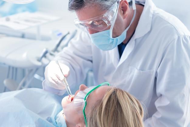 Dentista, examinando, um, dentes pacientes, com, máscara cirúrgica, e, luvas