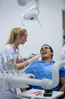 Dentista examinando um paciente com ferramentas