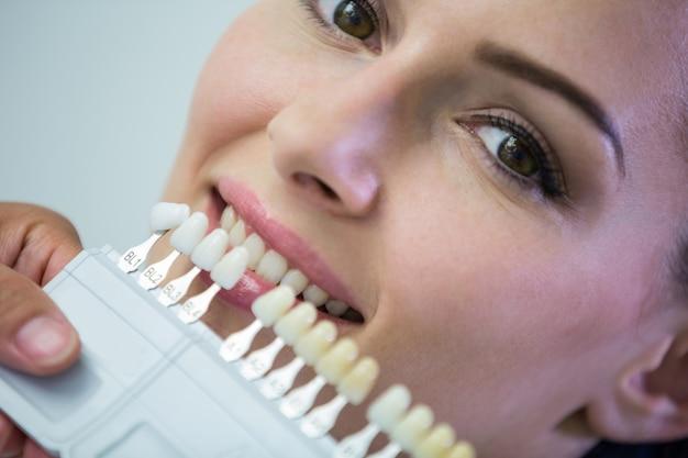 Dentista examinar paciente do sexo feminino com tons de dentes