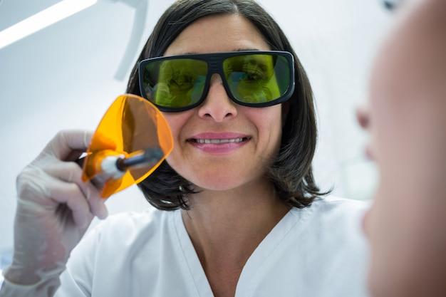 Dentista examinar pacientes dentes com luz de cura dental