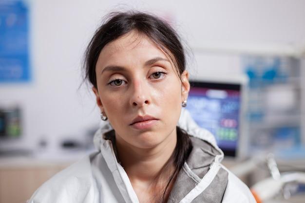 Dentista exausto, usando equipamento de proteção contra coronavírus, olhando para a câmera, especialidade médica cansada ...