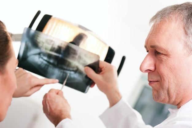 Dentista, explicando o raio-x para o paciente