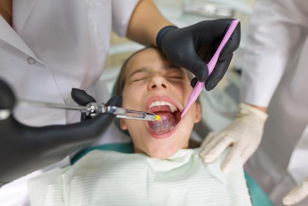 Dentista faz injeção de anestésico na gengiva
