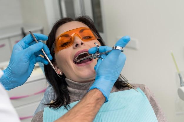 Dentista fazendo injeção de anestésico no paciente